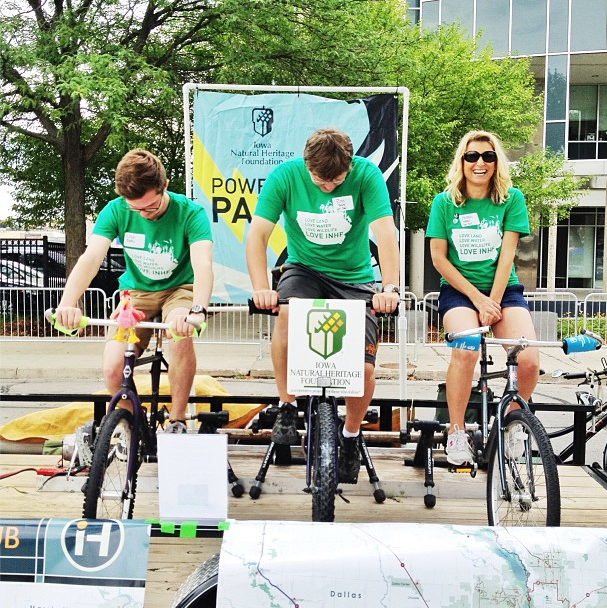 INHF's bike generator was a hit at the Des Moines stop of RAGBRAI, where it supplied the energy for a stereo and cell phone charging station.  Pictured (from left to right): Trails Intern, Josh Mades; Land Projects Associate Ross Baxter; and Communications Director Hannah Inman.