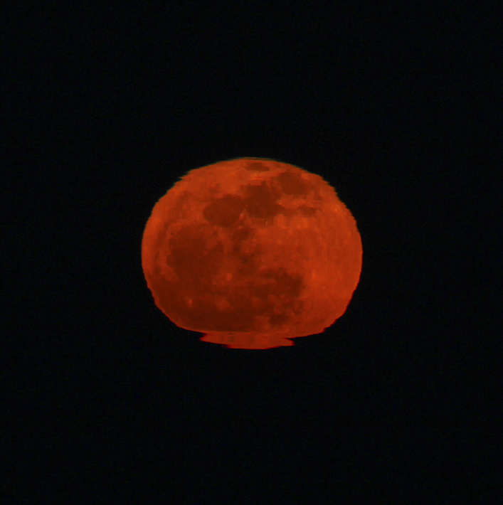 If you have watched the moon rise through the magnification of a pair of binoculars or a telescope, you may have noticed that it is not precisely circular in shape.  The dense atmosphere close to the earth's surface usually contains warm and cold air layers.   As the light passes through them, it may bend the light transmitted from the image and cause distortion.  The effect is readily apparent in this image and especially at the base of the moon.  The rich orange color is also an effect of atmospheric dust and haze or moisture in the air.