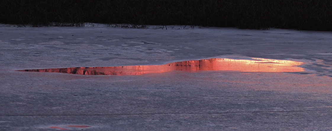 """On a small frozen pond the setting sun can produce dramatic reflections in surface melt water. The mirror-like surface of the water and its irregular shape are surrounded by the cold blue non-reflective surface of the ice. It is a fleeting event as the sunset sky fades into twilight."" – Carl Kurtz"